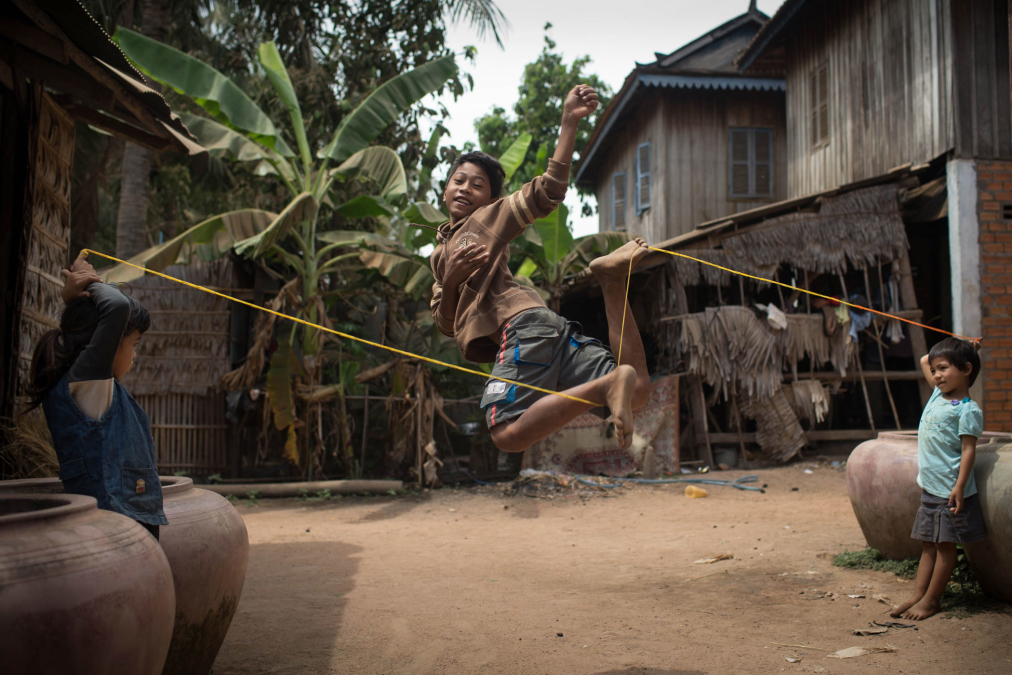 Boy jumping over a rope held by his sisters, Cambodia.