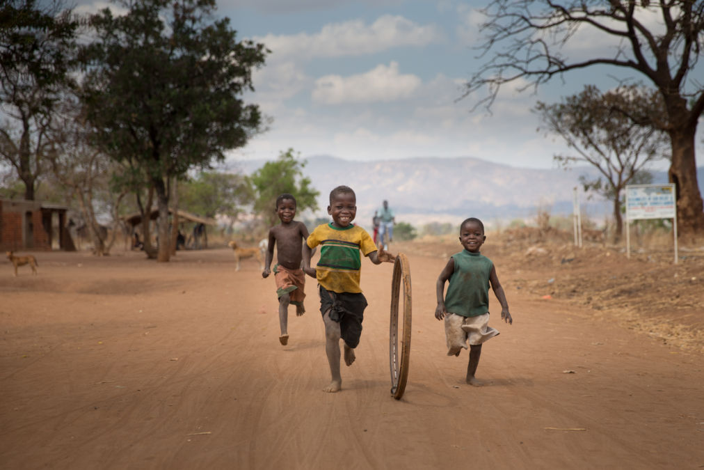 Children playing with an old bicycle wheel, Salima, Malawi.